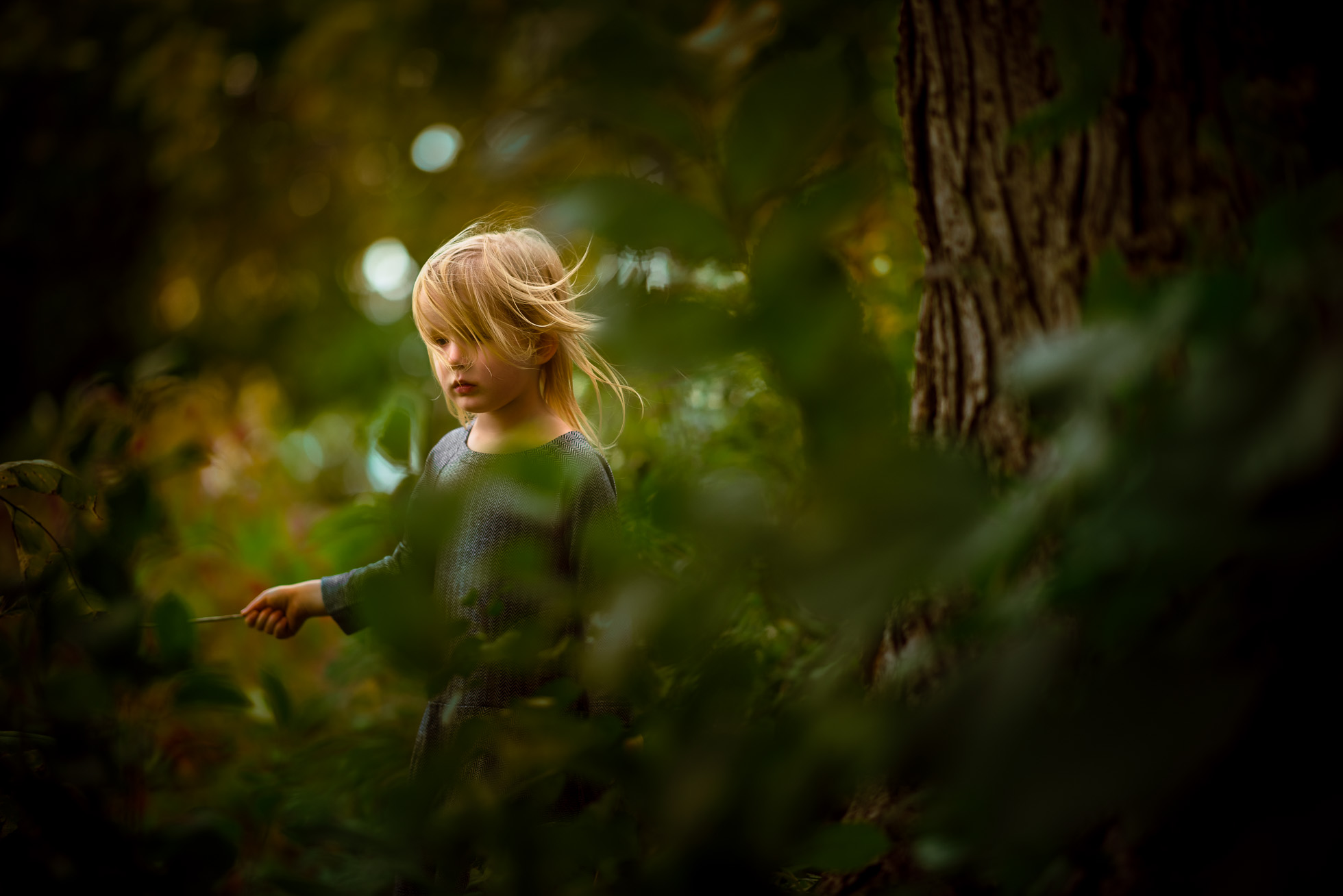 colorful-outdoor-natural-light-photo-of-hair-blowing-in-autumn-breeze-and-little-girl-framed-by-fall-leaves-by-sarah-wilkerson