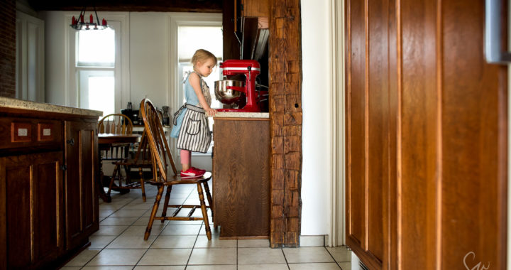 Everyday-Color-Natural-Light-Photo-of-Little-Girl-Making-Cookies-in-Empire-Red-Kitchenaid-Mixer-While-Wearing-Anthropologie-Apron-by-Sarah-Wilkerson-