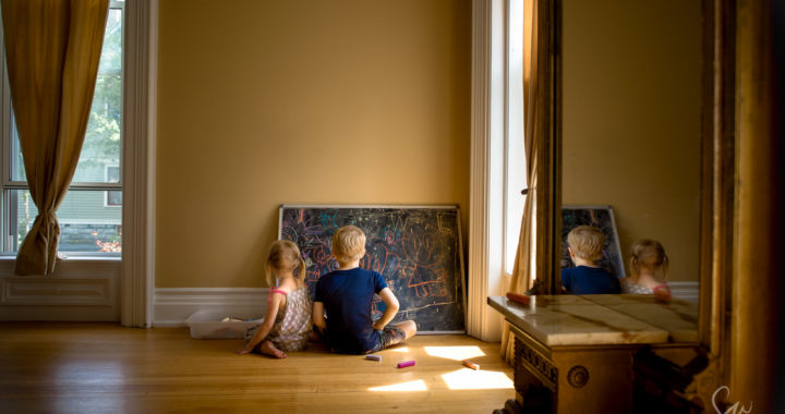 Everyday-Documentary-Photo-of-Brother-and-Sister-Coloring-on-Chalkboard-with-Chalk-in-Beautiful-Ornate-Natural-Light-Room-by-Sarah-Wilkerson-