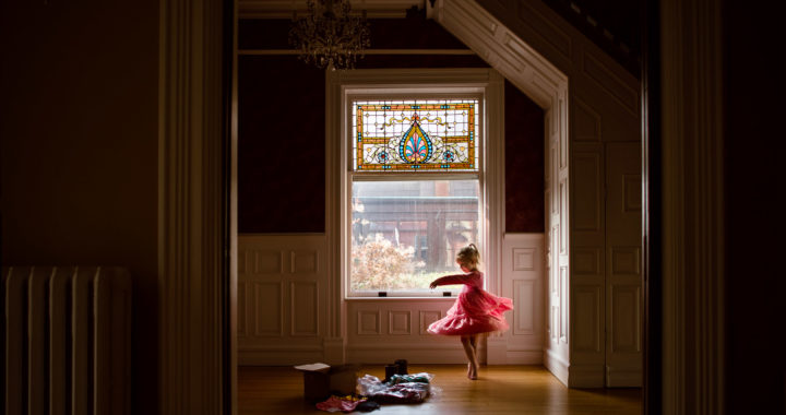 everyday-documentary-photo-of-little-girl-prentending-to-be-ballerina-twirling-in-pink-dress-while-trying-on-new-clothes-in-beautiful-window-light-by-sarah-wilkerson