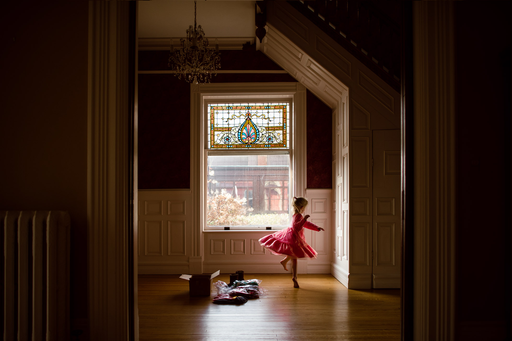everyday-documentary-photo-of-little-girl-prentending-to-be-ballerina-twirling-in-pink-dress-while-trying-on-new-clothes-in-beautiful-window-light-by-sarah-wilkerson-2