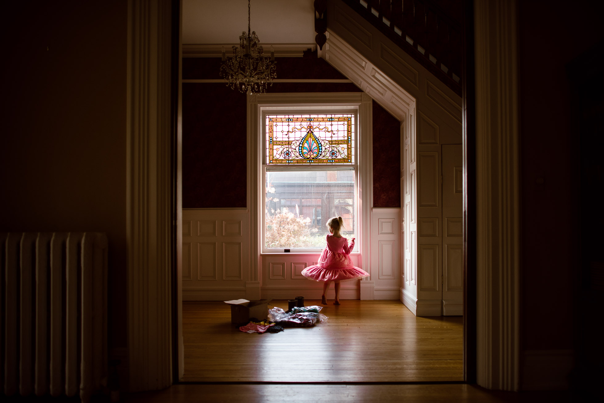 everyday-documentary-photo-of-little-girl-prentending-to-be-ballerina-twirling-in-pink-dress-while-trying-on-new-clothes-in-beautiful-window-light-by-sarah-wilkerson-3338