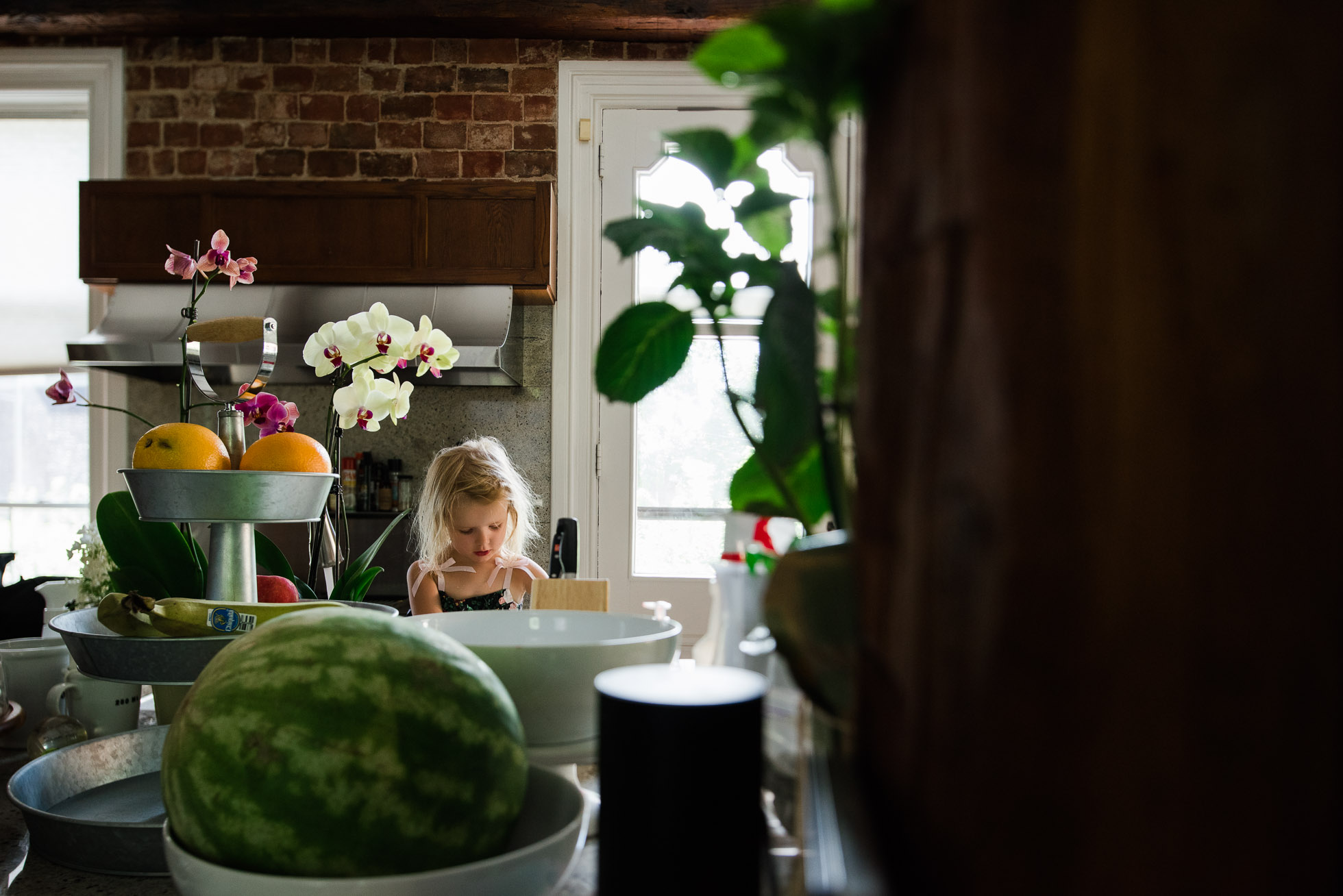 Everyday-Documentary-Tilt-Shift-Photo-of-Little-Girl-in-Kitchen-with-Colorful-Summer-Fruit-and-Flowers-by-Sarah-Wilkerson-