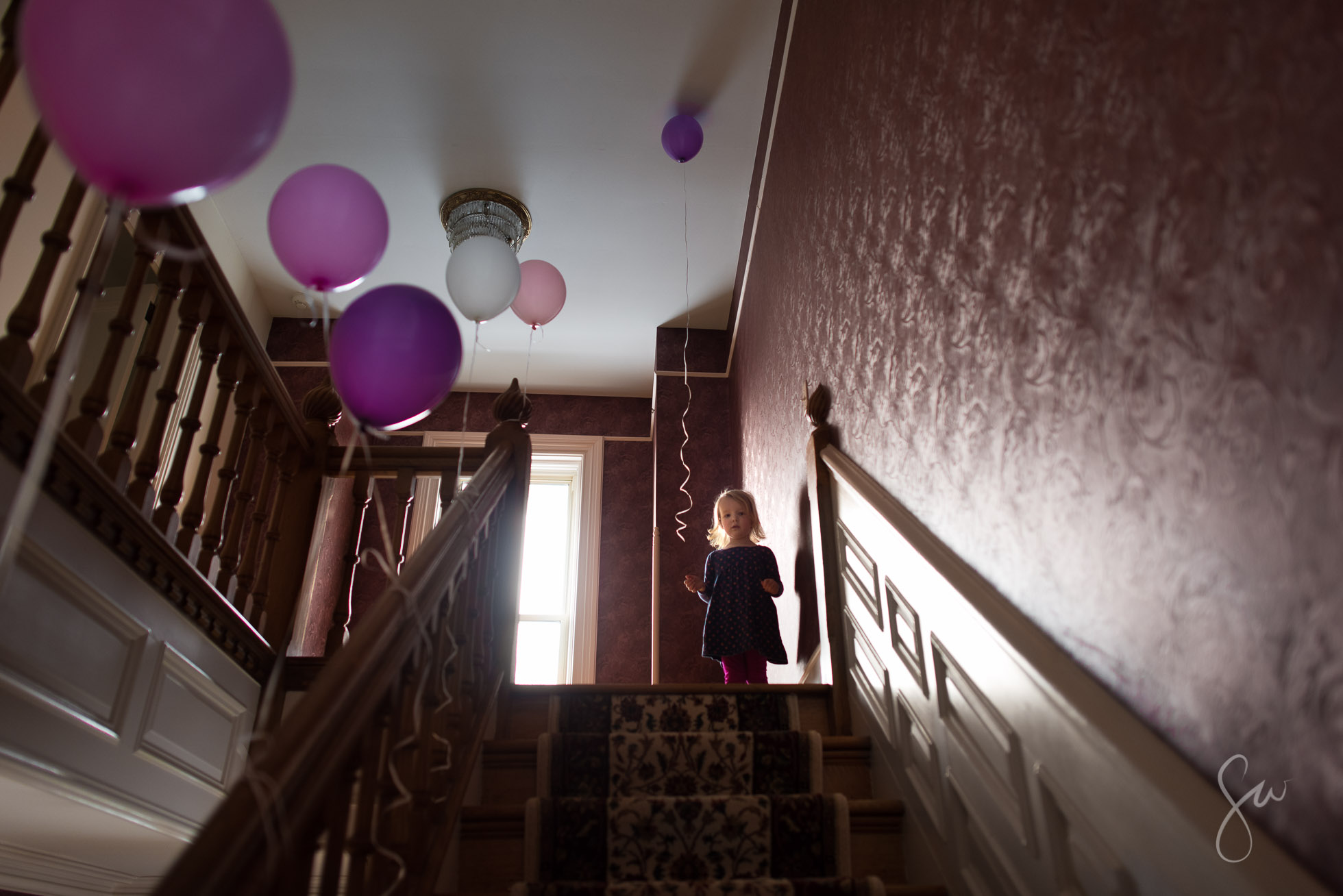 Everyday-Photo-of-Three-Year-Old-Celebrating-Her-Birthday-with-Pink-and-Purple-Balloons-3372