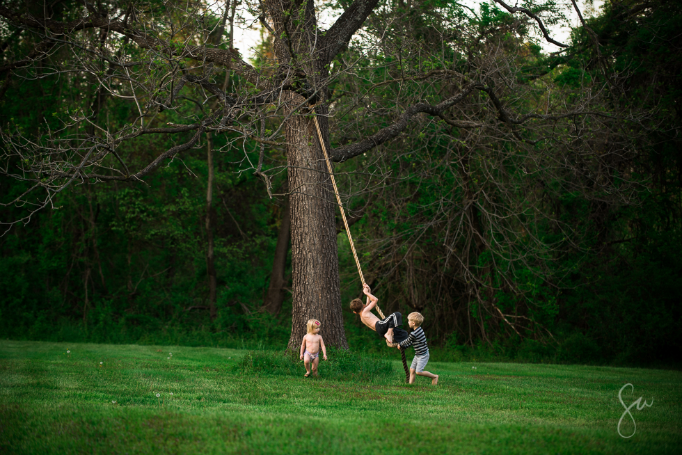 Kids Climbing A Rope Hanging From A Tree
