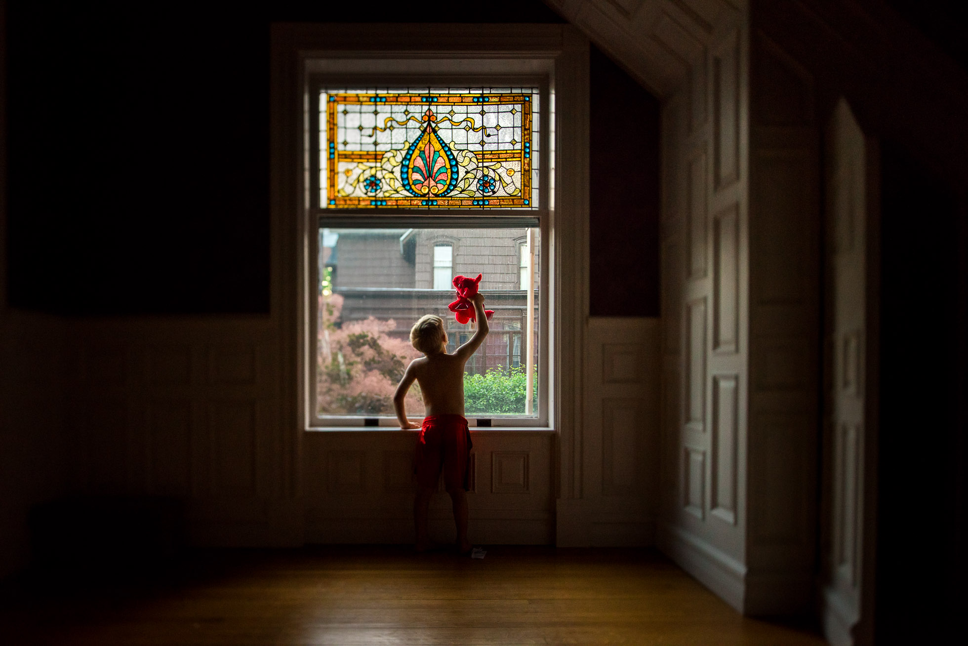 Little-Boy-Playing-with-Red-Dragon-Toy-in-Front-of-Beautiful-Stained-Glass-Window-in-Low-Light-by-Sarah-Wilkerson-8115