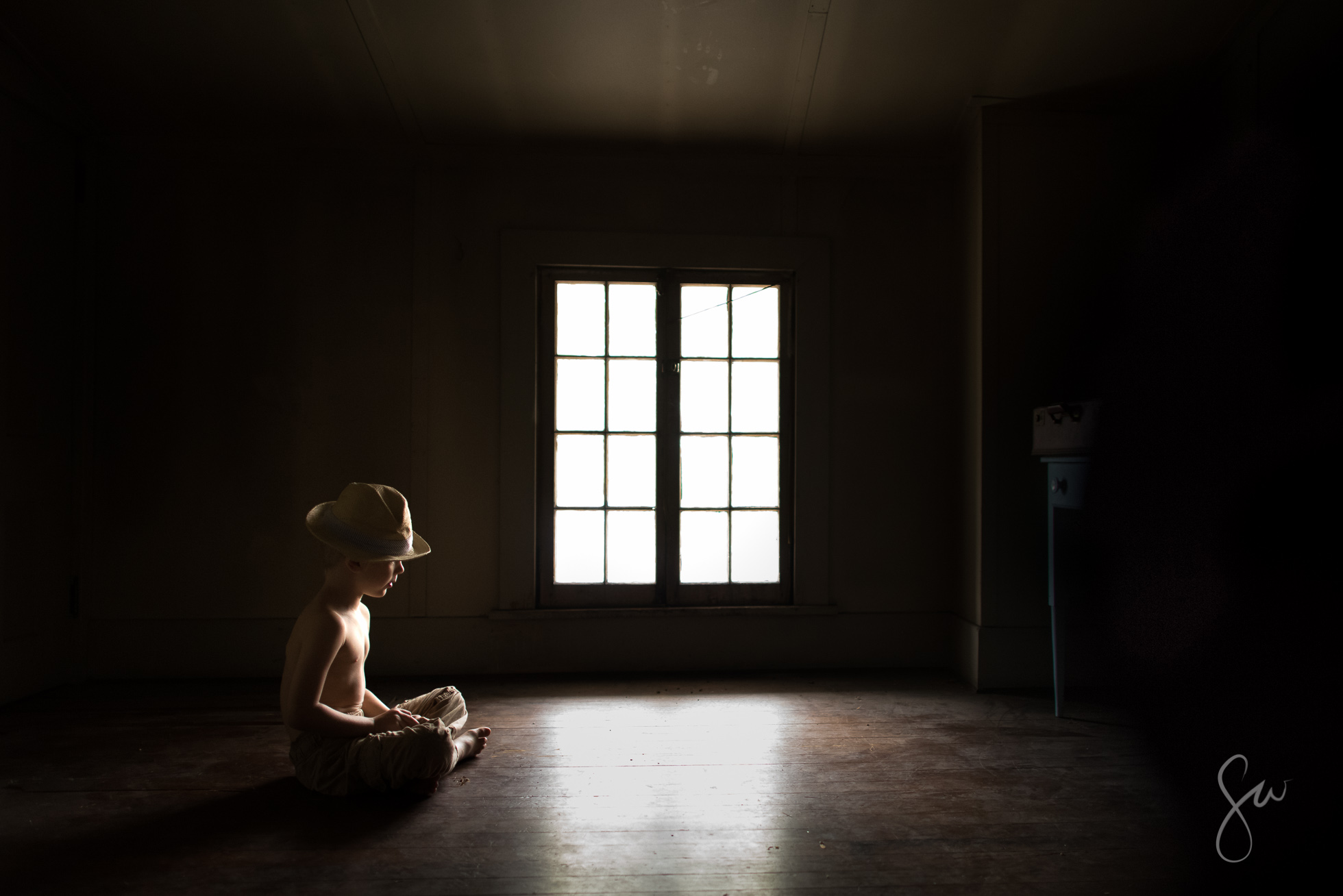 Little-Boy-Wearing-Hat-Sitting-in-Creepy-Low-Light-Attic-by-Photographer-Sarah-Wilkerson-1089