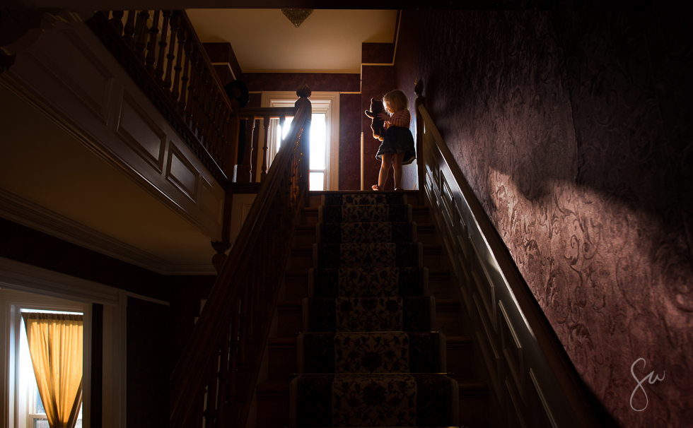 Little-Girl-Holding-a-Teddy-Bear-at-the-Top-of-Ornate-Staircase-in-Beautiful-Light-