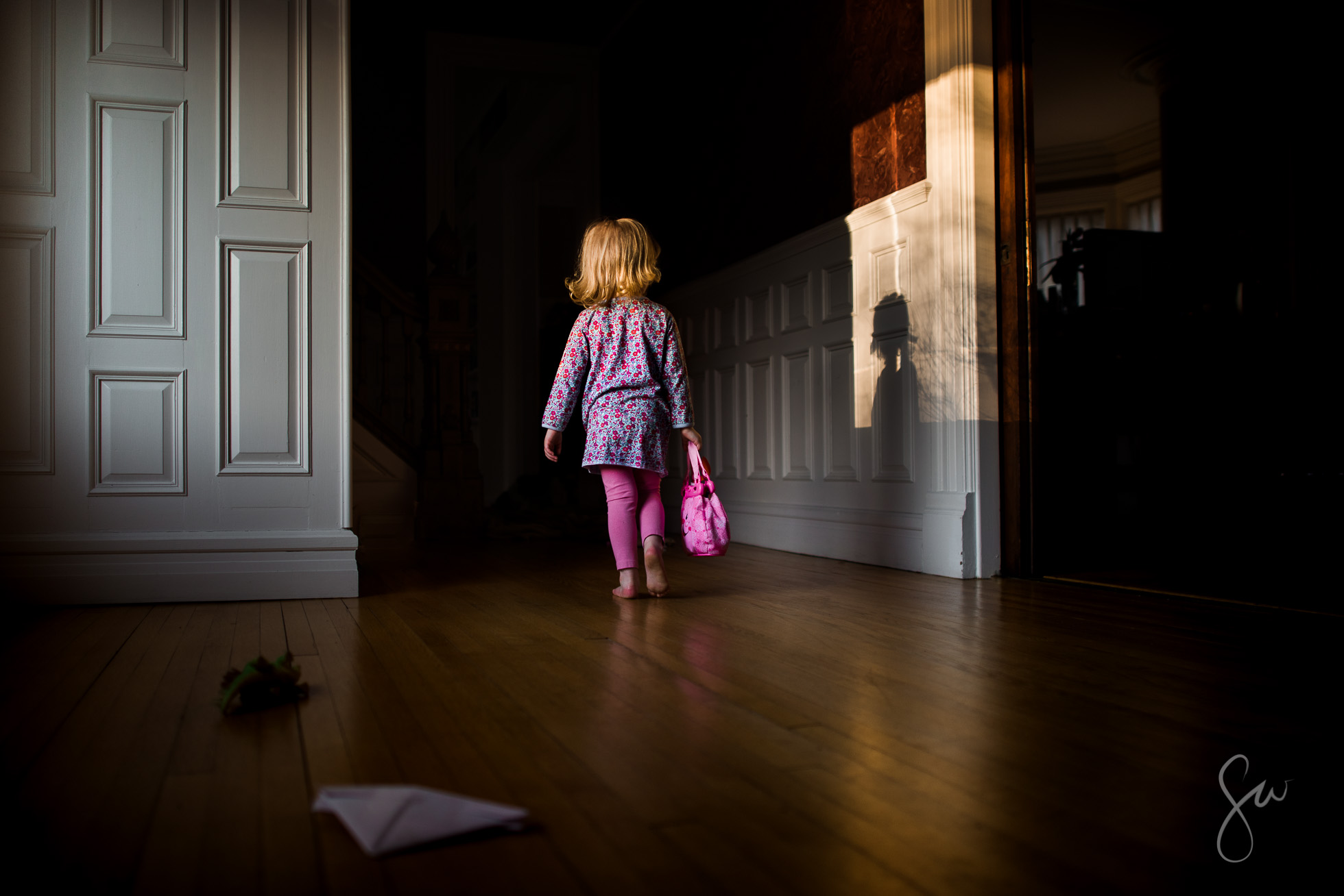 Little-Girl-Playing-Grown-Up-with-Pink-Purse-and-Blonde-Curls-in-Dramatic-Light-with-Shadow-3286