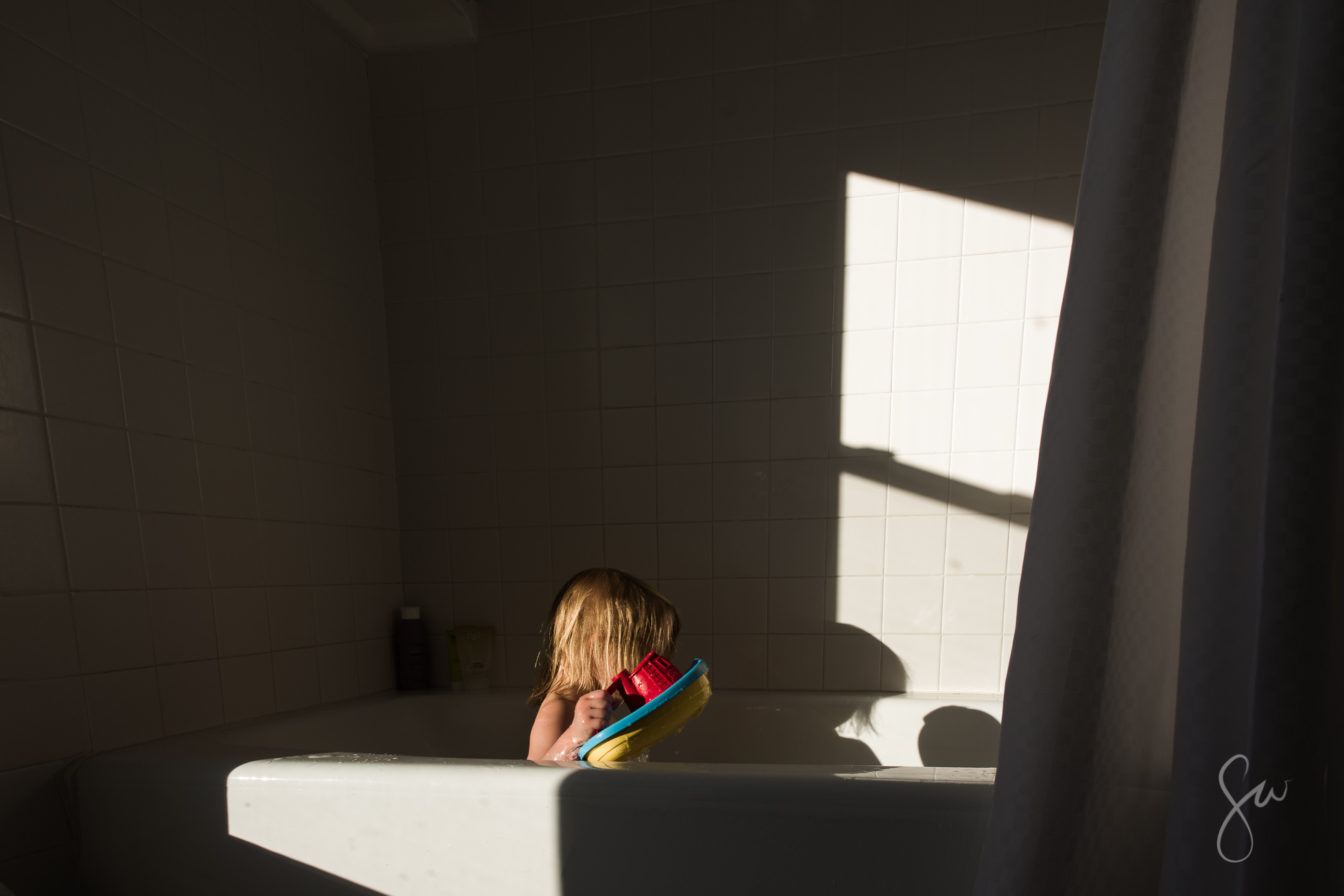 Little-Girl-Playing-with-Colorful-Tub-Toys-Boat-in-White-Bathtub-with-Amazing-Shadows-and-Beautiful-Light-by-Sarah-Wilkerson-