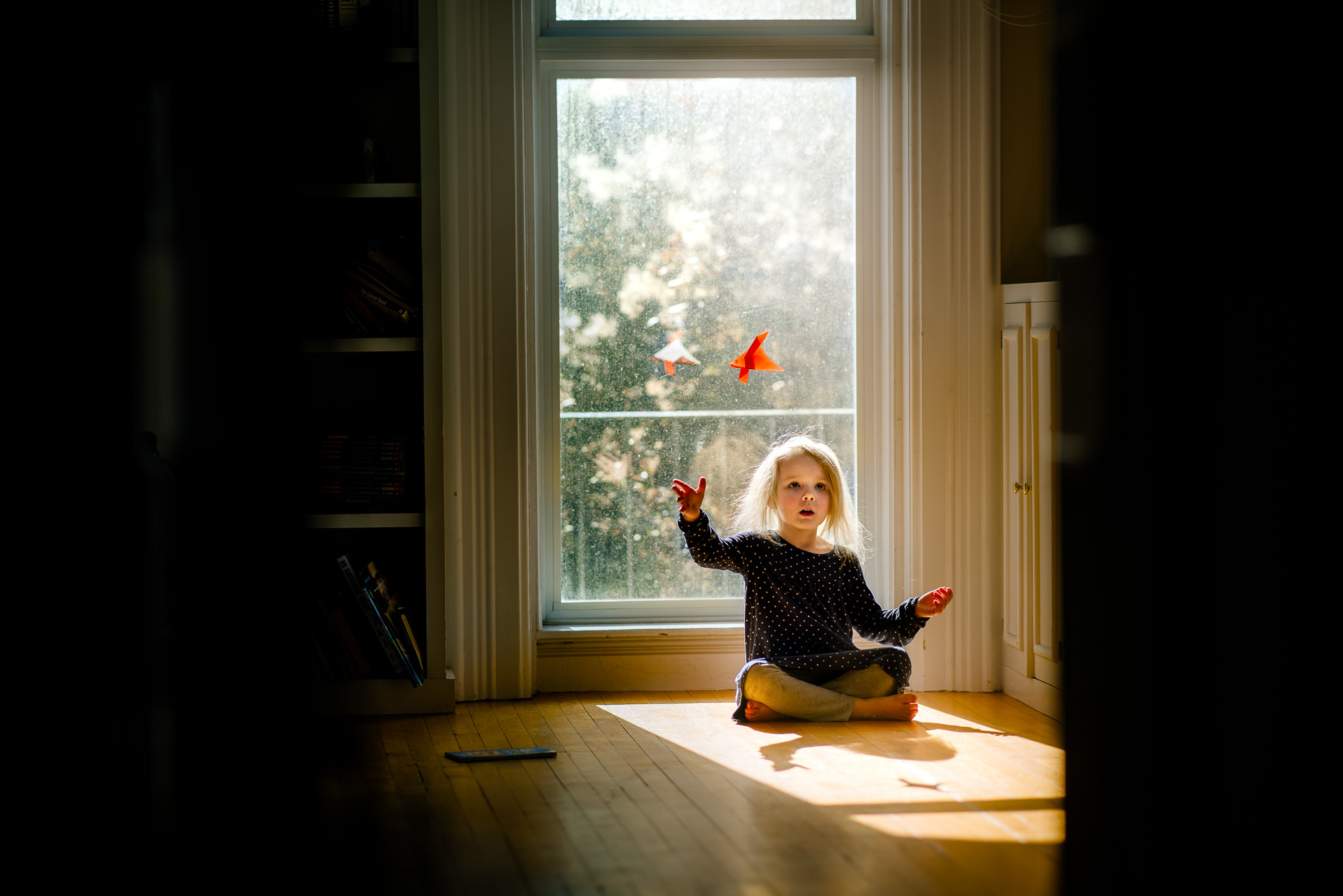little-girl-playing-with-orange-origami-swan-near-tall-window-with-beautiful-natural-light-backlighting-by-sarah-wilkerson