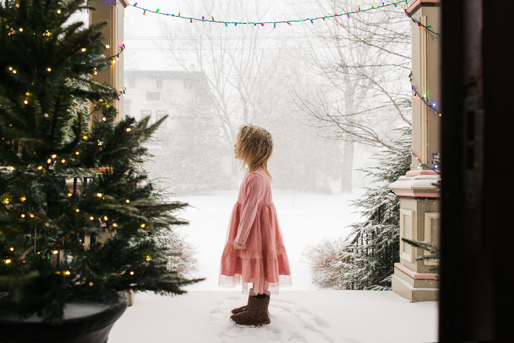 little-girl-in-pink-dress-standing-on-porch-and-watching-snowflakes-during-blizzard-with-christmas-light-by-sarah-wilkerson