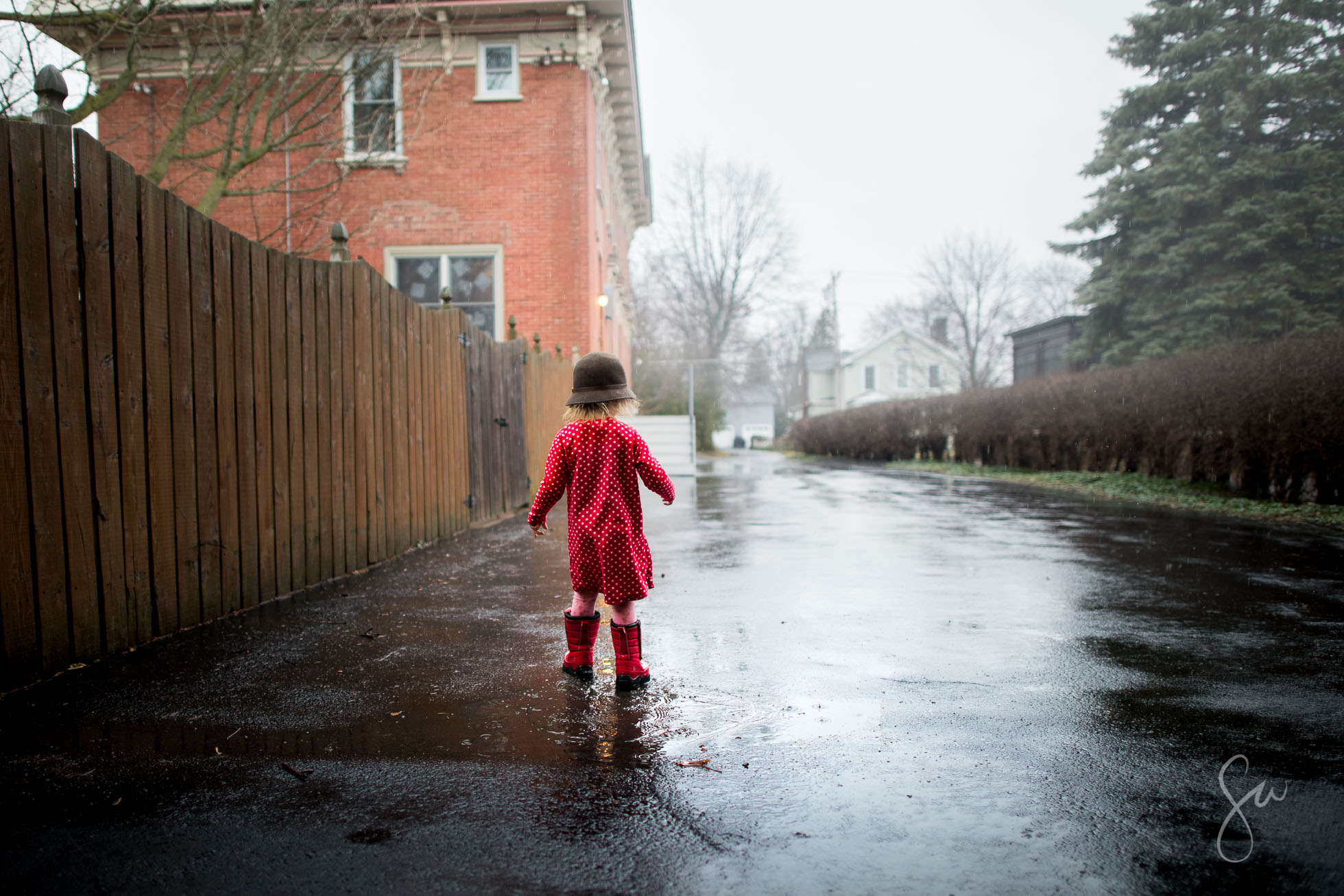 Little-Girl-in-Polka-Dots-Red-Boots-and-a-Cloche-Hat-Playing-outside-on-a-rainy-day-3745