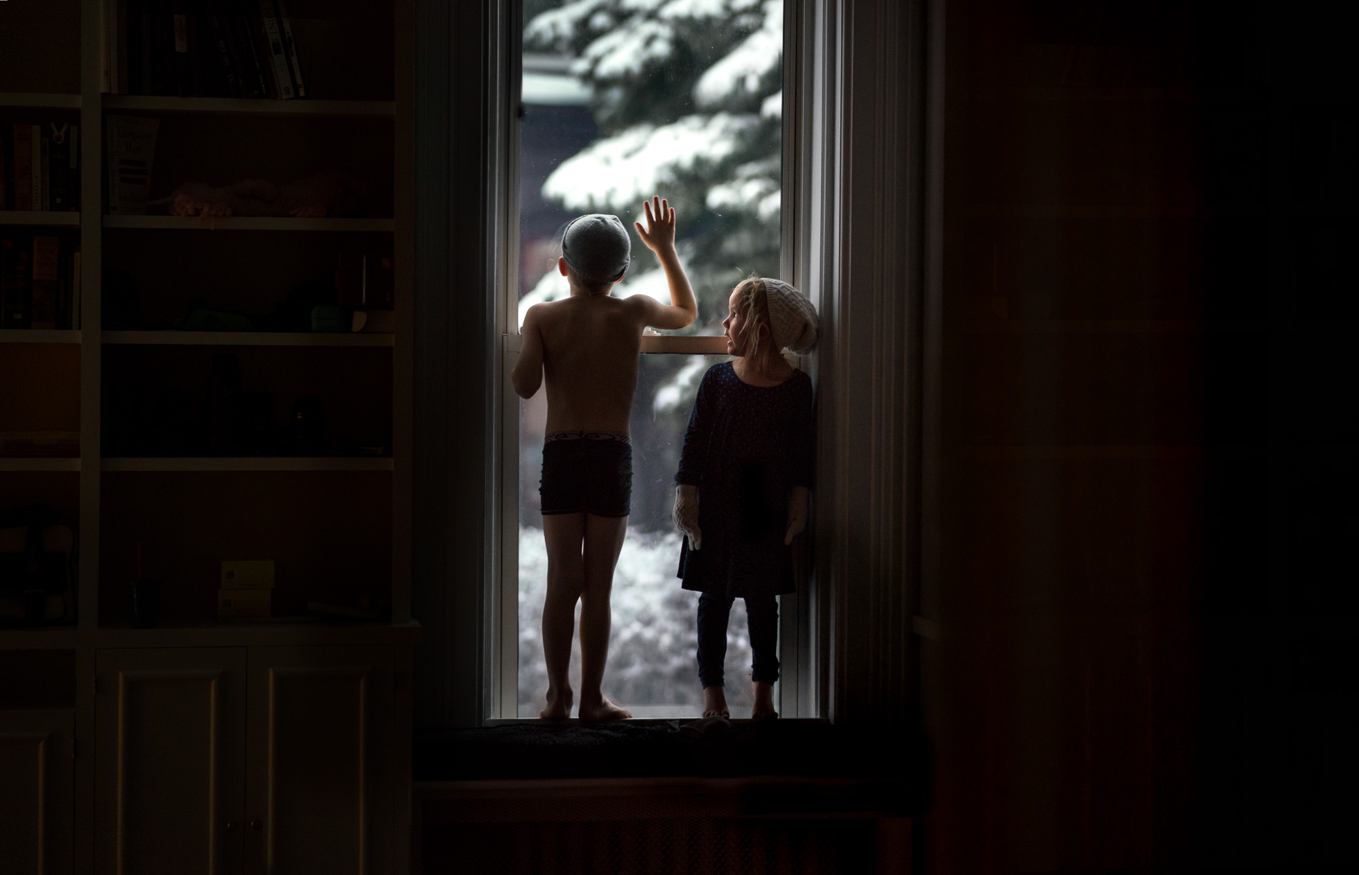 low-light-documentary-photo-of-brother-and-sister-looking-outside-window-after-playing-in-the-snow-on-a-snow-winter-day-by-sarah-wilkerson
