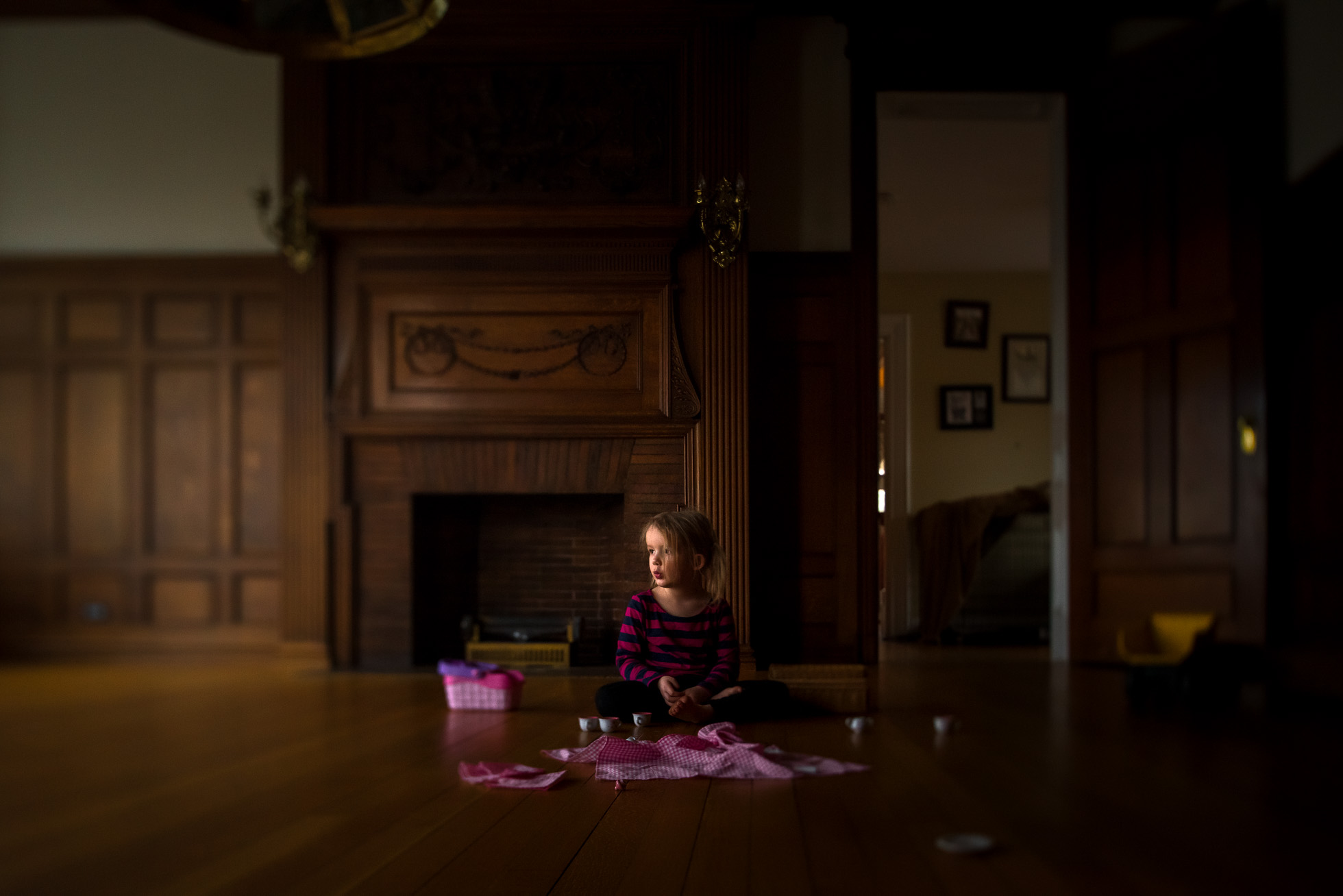 tilt-shift-everyday-environmental-portrait-of-little-girl-having-tea-party-picnic-in-beautiful-old-fashioned-wood-paneled-room-with-pretty-light-and-pink-colors-by-sarah-wilkerson